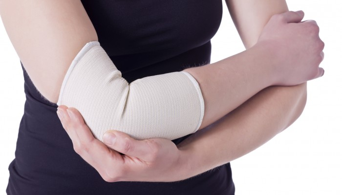 Image of an athlete woman having an elbow pain wrapped with a bandage against the white background