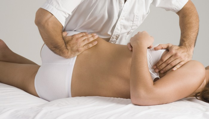 Chiropractor adjusting woman's back