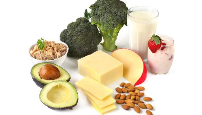 Calcium-rich foods on white background. Includes avocado salmon broccoli milk yogurt cheeses and almonds.
