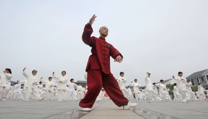 A man leads participants to perform Taiji, a traditional form of Chinese martial arts, in Liu'an, Anhui province July 13, 2008. Some residents from a local community attended the performance to celebrate the upcoming 2008 Beijing Olympic Games, China Daily reported. REUTERS/China Daily (CHINA).  CHINA OUT. NO COMMERCIAL OR EDITORIAL SALES IN CHINA.