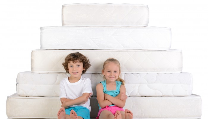 Young children sitting on lots of mattresses isolated on white background