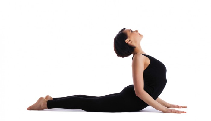 young woman training in yoga asana - cobra bhujangasana pose