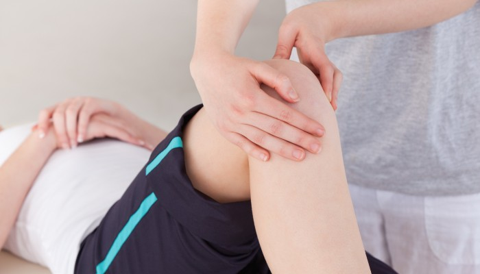 Masseuse massing the knee of a sportswoman