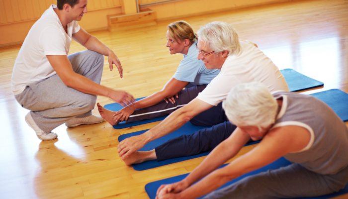 Fitnesstrainer gibt Gruppe im Fitnesscenter Anleitungen