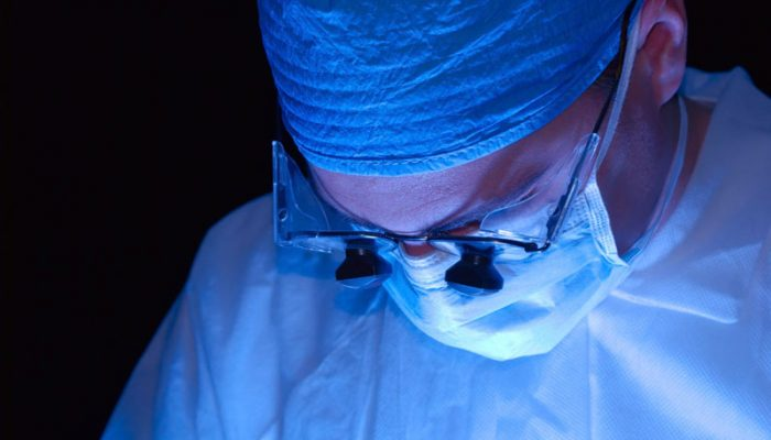 Surgeon or doctor wearing magnifying glasses to work.  Lit from beneath with a black background.